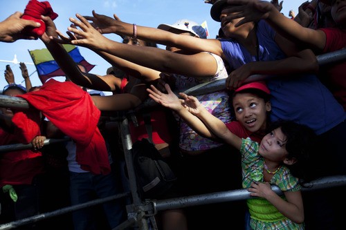 Supporters reach out for campaign swag as they wait for Venezuela's President Hugo Chavez to deleiver his speech at a campaign rally in Guarenas, Venezuela, Saturday, Sept. 29, 2012. Venezuela's presidential election is scheduled for Oct. 7. (AP Photo/Rodrigo Abd)