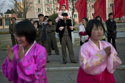 A North Korean child covers the eyes of her father as she sits on his shoulders watching mass folk dancing in front of Pyongyang Indoor Stadium in Pyongyang, North Korea, on Monday, April 15, 2013. Oblivious to international tensions over a possible North Korean missile launch, Pyongyang residents spilled into the streets Monday to celebrate a major national holiday, the birthday of their first leader, Kim Il Sung. (AP Photo/David Guttenfelder)