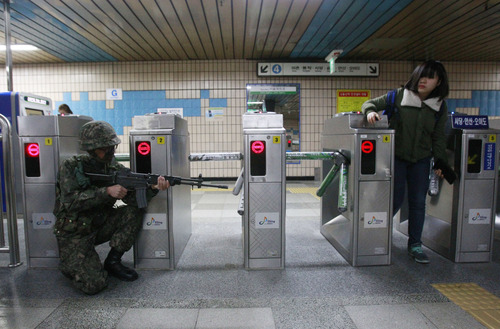 A South Korean army soldier aims his machine gun as a passenger goes through a ticket barrier during an anti-terrorism drill against possible terrorists' attacks at a subway station in Seoul, South Korea, Monday, April 15, 2013. Oblivious to international tensions over a possible North Korean missile launch, Pyongyang residents spilled into the streets Monday to celebrate a major national holiday, the birthday of their first leader, Kim Il Sung. Elsewhere in the region, however, the focus remained on the threat of a missile launch as U.S. Secretary of State John Kerry wrapped up a tour to coordinate Washington's response with Beijing, North Korea's most important ally, as well as Seoul and Tokyo. (AP Photo/Ahn Young-joon)