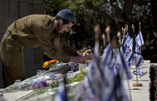 An Israeli soldier lights a candle at the grave of a relative during a ceremony marking Memorial Day on the Mount of Olives overlooking Jerusalem's Old City, Monday, April 15, 2013. Israelis paused to honor and remember friends and relatives Monday as sirens wailed across the country and solemn Memorial Day ceremonies were held for fallen soldiers and victims of terrorism. (AP Photo/Sebastian Scheiner)