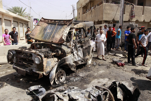 Civilians gather at the scene of a car bomb attack in the east Baghdad neighborhood of Kamaliya, Iraq, Monday, April 15, 2013. A series of attacks across, Iraq many involving car bombs, has killed and wounded dozens of people, police said less than a week before Iraqis in much of the country are scheduled to vote in the country's first elections since the 2011 U.S. troop withdrawal. (AP Photo/ Khalid Mohammed)