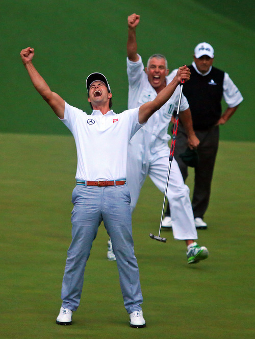 Adam Scott and his caddie Steve Williams reacts to his putt dropping on the second hole of a playoff to win the Masters golf tournament, Sunday, April 14, 2013, in Augusta. Runner-up Angel Cabrera watches in the background. Scott became the first Australian to win the Masters. (AP Photo/Atlanta Journal-Constitution, Curtis Compton)  MARIETTA DAILY OUT; GWINNETT DAILY POST OUT; LOCAL TV OUT; WXIA-TV OUT; WGCL-TV OUT