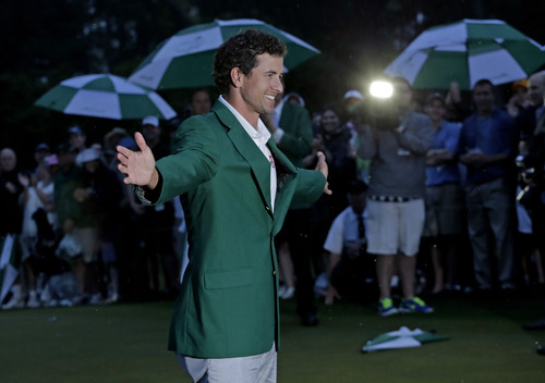 Adam Scott, of Australia, celebrates with his  green jacket after winning the Masters golf tournament Sunday, April 14, 2013, in Augusta, Ga.  (AP Photo/Charlie Riedel)