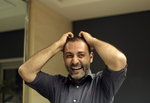 Associated Press photographer Khalil Hamra reacts after hearing that his photographs were part of an Associated Press team entry that won the Pulitzer prize for their photographs from Syria, in Cairo, Egypt, Monday, April 15, 2013. The Pulitzer in breaking news photography went to The Associated Press for its coverage of the civil war in Syria.(AP Photo/Maya Alleruzzo)