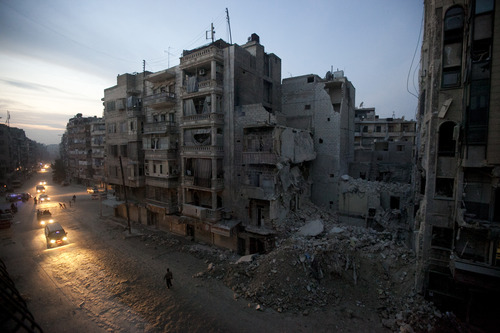 FILE - Night falls on a Syrian rebel-controlled area of Aleppo, Nov. 29, 2012, as destroyed buildings, including Dar Al-Shifa hospital, are seen on Sa'ar street after airstrikes targeted the area a week before. This image was one in a series of 20 by AP photographers that won the 2013 Pulitzer Prize in Breaking News Photography. (AP Photo/Narciso Contreras, File)