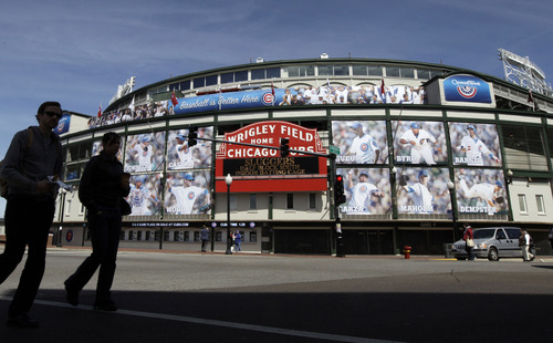 FILE - In this April 4, 2012 file photo, people walk outside Wrigley Field in Chicago. Two people with knowledge of the negotiations between the Ricketts family that owns the Chicago Cubs and the city say the two are near an agreement on a $500 million project at Wrigley Field. The people spoke Friday, April 5, 2013, on condition of anonymity because the deal was not yet finished and they are not authorized to publicly discuss it. The deal calls for $300 million in renovations at Wrigley and a $200 million hotel nearby. (AP Photo/Nam Y. Huh, File)