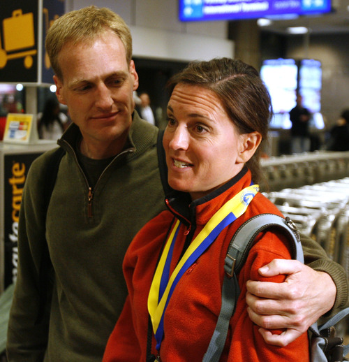 Rick Egan  | The Salt Lake Tribune   Mike Davey hugs his wife Kellie Davey at the Salt Lake International Airport, after they returned from Boston Monday evening, April 15, 2013.  Kellie had just finished the Boston Marathon, when the explosions went off.