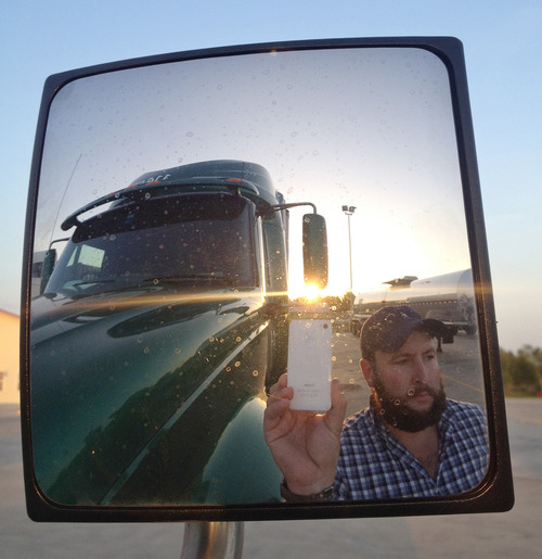 """This undated image provided by James Weitze shows a truck driver taking a self portrait on the road. Weitze satisfies his video fix with an iPhone. He sleeps most of the time in his truck, and has no apartment. To be sure, he's an extreme case and probably wouldn't fit into Nielsen's definition of a household in the first place. But he's watching Netflix enough to keep up on shows like """"Weeds,"""" """"30 Rock,"""" """"Arrested Development,"""" """"Breaking Bad,"""" """"It's Always Sunny in Philadelphia"""" and """"Sons of Anarchy."""" (AP Photo/James Weitze)"""