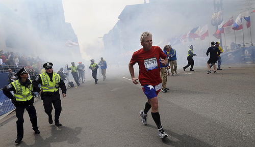 A Boston Marathon competitor and Boston police run from the area of an explosion near the finish line in Boston, Monday, April 15, 2013. (AP Photo/MetroWest Daily News, Ken McGagh)