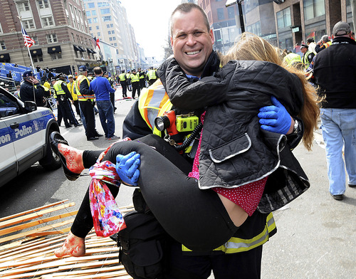 In this Monday, April 15, 2013 photo, Boston Firefighter James Plourde carries an injured girl away from the scene after a bombing near the finish line of the Boston Marathon in Boston. The FBI's investigation into the bombings at the Boston Marathon was in full swing Tuesday, with authorities serving a warrant on a suburban Boston home and appealing for any private video, audio and still images of the blasts that killed at least three and wounded more than 170. (AP Photo/MetroWest Daily News, Ken McGagh)
