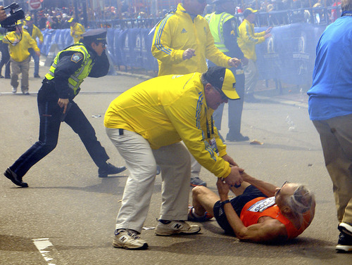 In this Monday, April 15, 2013 photo, a race official assists Bill Iffrig, 78, of Lake Stevens, Wash., as Iffrig lies on the ground after the first explosion, as police officers react to a second explosion at the finish line of the Boston Marathon in Boston, Monday, April 15, 2013.  Iffrig, of Lake Stevens, Wash., was running his third Boston Marathon and near the finish line when he was knocked down by one of two bomb blasts. (AP Photo/MetroWest Daily News, Ken McGagh)