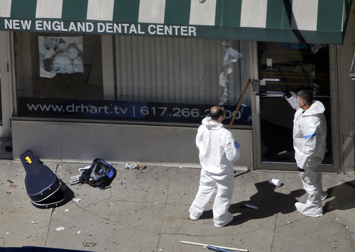 Two men in haz-mat suits investigate the scene near the first bombing on Boylston Street in Boston Tuesday, April 16, 2013 near the finish line of the 2013 Boston Marathon, a day after two blasts nearby killed at least three and injured over 170 people. (AP Photo/Elise Amendola)