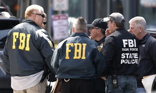 FBI agents gather near the finish line of the Boston Marathon in Boston Tuesday, April 16, 2013. The bombs that ripped through the crowd at the Boston Marathon, killing at least three people and wounding more than 170, were fashioned out of pressure cookers and packed with shards of metal, nails and ball bearings to inflict maximum carnage, a person briefed on the investigation said Tuesday. (AP Photo/Winslow Townson)