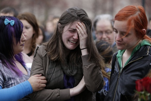 Emma MacDonald, 21, center, reacts while remembering the victims of the Boston Marathon explosions during a vigil at Boston Common, Tuesday, April 16, 2013, one day after bombs exploded at the finish line of the marathon. (AP Photo/Julio Cortez)