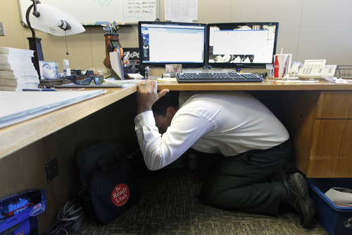 Al Hartmann  |  The Salt Lake Tribune Ryan Longman, a manager with the State of Utah Deparment of Public Safety ducks under his desk and covers his head during the Great Utah Shake Out, an earthquake simulation excercise at the Utah State Capitol Wednesday April 17.