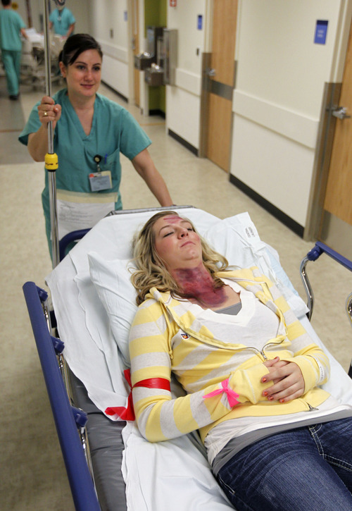 "Al Hartmann  |  The Salt Lake Tribune Cyprus High School drama student plays the part of an injured person who was unconscious with a chest wound during the Utah Shake Out earthquake excercise Wednesday morning April 17 at LDS Hospital.  She was tagged ""red"" in a triage area and was transported directly for emergency care."