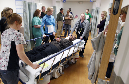 Al Hartmann  |  The Salt Lake Tribune Mock patient with a spinal cord injury is wheeled into a trauma center for assesment during the Utah Shake Out earthquake excercise Wednesday morning April 17 at LDS Hospital.