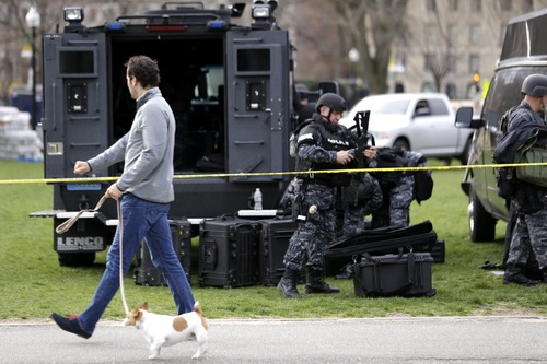 A man walks a dog as officials suit up in tactical gear at Boston Common, Tuesday, April 16, 2013, one day after bombs exploded at the finish line of the Boston Marathon. A vigil is expected at Boston Common later in the day to honor the victims of the two bombs that blew up within about 10 seconds and about 100 yards apart Monday near the finish line of the race. (AP Photo/Julio Cortez)