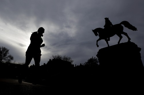 A woman jogs near a statue of George Washington at Boston Common, Tuesday, April 16, 2013, one day after bombs exploded at the finish line of the Boston Marathon. A vigil is expected at Boston Common later in the day to honor the victims of the two bombs that blew up within about 10 seconds and about 100 yards apart Monday near the finish line of the race. (AP Photo/Julio Cortez)