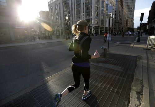 A jogger trots near the corner of Berkeley Street and Boylston Street not far from the finish line of the Boston Marathon, Wednesday, April 17, 2013, in Boston. The city continues to cope following Monday's explosions near the finish line of the marathon. (AP Photo/Julio Cortez)