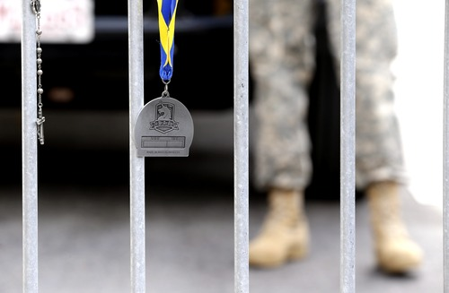 A Rosary, left, hangs from a barricade near a Boston Marathon finisher's medal, center,guarded by a Massachusetts National Guard member near a makeshift memorial on Boylston Streetnear the site where a day earlier explosions killed at least three and injured more than 140 in Boston, Tuesday, April 16, 2013.   (AP Photo/Julio Cortez)