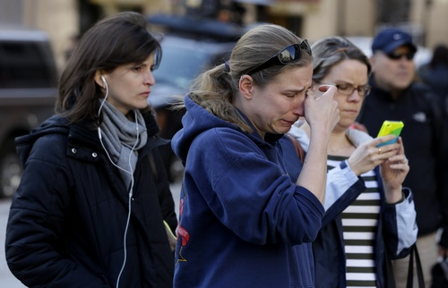 Jillian Blenis, 30, center, of Boston, reacts while stopping at a makeshift memorial, Wednesday, April 17, 2013, in Boston. The city continues to cope following Monday's explosions near the finish line of the Boston Marathon. (AP Photo/Julio Cortez)