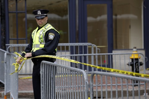 A Boston Police officer ties caution tape in the downtown area near Copley Square, Tuesday, April 16, 2013, one day after a pair of bombs exploded at the finish line of the Boston Marathon. Two bombs blew up within about 10 seconds and around 100 yards apart Monday near the finish line of the race. (AP Photo/Julio Cortez)