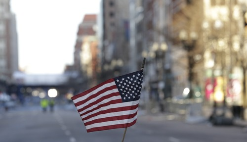 A flag sits on a barricade on Boylston Street near the finish line of the Boston Marathon, Wednesday, April 17, 2013, in Boston. The city continues to cope following Monday's explosions near the finish line of the marathon. (AP Photo/Julio Cortez)