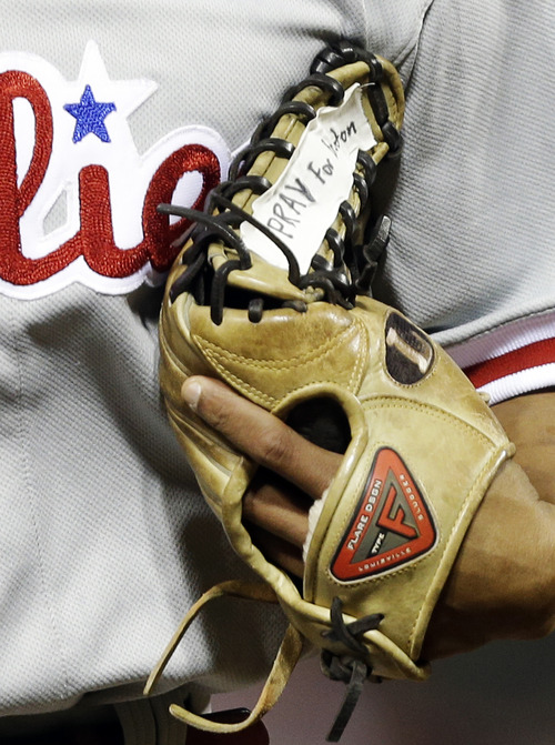Philadelphia Phillies center fielder Ben Revere runs off the field with tape on his glove that says 'Pray for Boston,' for the victims of the Monday bombings at the Boston Marathon, in the fifth inning of a baseball game against the Cincinnati Reds, Tuesday, April 16, 2013, in Cincinnati. (AP Photo/Al Behrman)