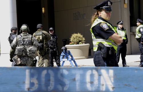 Officials in tactical gear stand guard behind a Boston Police Department barricade near the site of the Boston Marathon explosions, Wednesday, April 17, 2013, in Boston. The city continues to cope following Monday's explosions near the finish line of the marathon.  Authorities investigating the deadly bombings have recovered a piece of circuit board that they believe was part of one of the explosive devices, and also found the lid of a pressure cooker that apparently was catapulted onto the roof of a nearby building, an official said Wednesday. (AP Photo/Julio Cortez)