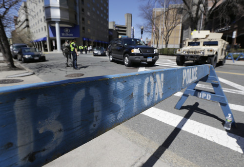 Officials stand guard near the site of the Boston Marathon explosions, Wednesday, April 17, 2013, in Boston. Authorities investigating the deadly bombings have recovered a piece of circuit board that they believe was part of one of the explosive devices, and also found the lid of a pressure cooker that apparently was catapulted onto the roof of a nearby building, an official said Wednesday. (AP Photo/Julio Cortez)
