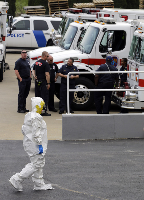 A Prince George's County, Md. firefighter dressed in a protective suit walks past emergency personell into a government mail screening facility in Hyattsville, Md., Wednesday, April 17, 2013. Police swept across the U.S. Capitol complex to chase a flurry of reports of suspicious packages and envelopes Wednesday after preliminary tests indicated poisonous ricin in two letters sent to President Barack Obama and a Mississippi senator.  (AP Photo/Alex Brandon)