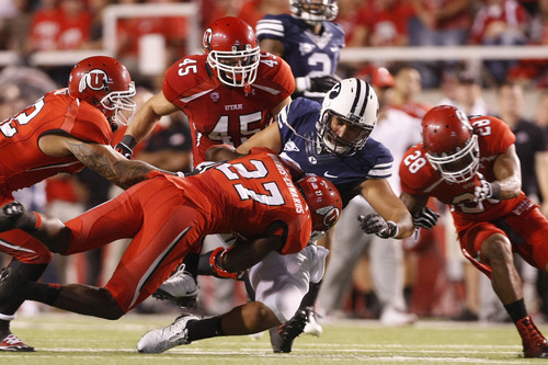 Chris Detrick  |  The Salt Lake Tribune Brigham Young Cougars tight end Kaneakua Friel (82) is tackled by Utah Utes linebacker LT Filiaga (42) Utah Utes defensive back Tyron Morris-Edwards (27) Utah Utes linebacker Boo Andersen (45) and Utah Utes defensive back Reggie Topps (28) during the first half of against BYU at Rice-Eccles Stadium Saturday September 15, 2012.  The score is 7-7 at halftime.