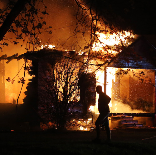 A person looks on as emergency workers fight a house fire after a nearby fertilizer plant exploded Wednesday, April 17, 2013, in West, Texas. (AP Photo/Waco Tribune Herald, Rod Aydelotte)