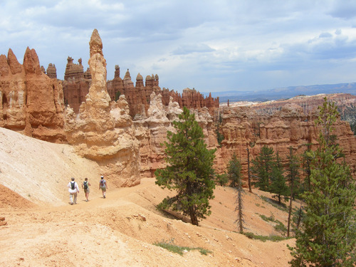 """Hikers approach """"hoodoos"""" on the Peekaboo Trail in Bryce Canyon National Park. Photo by Jason Bergreen."""