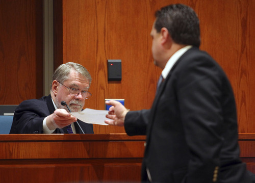 Dr. Jeffrey Saffle hands Davis County Attorney Troy Rawlings a document during final day of Nathan Sloop's preliminary hearing in the death of Ethan Stacy at Second District Court Friday, April 19, 2013 in Farmington, Utah.  (NICK SHORT/Standard-Examiner)