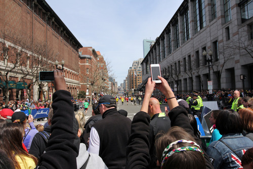 In this Monday, April 15, 2013, photo, spectators make pictures with camera phones during the Boston Marathon in Boston, before two bombs exploded at the finish line in an attack that killed 3 people and wounded over 170. As the investigation of the Boston Marathon bombings illustrates, getting lost in the crowd is no longer an easy feat. There are eyes _ and cameras _ everywhere. (AP Photo/Kenshin Okubo)