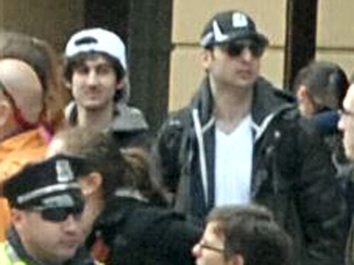 This photo released by the FBI early Friday April 19, 2013, shows what the FBI is calling suspect 1, in black cap, and suspect number 2, in white cap, walking through the crowd in Boston on Monday, April 15, 2013, before the explosions at the Boston Marathon. (AP Photo/FBI)