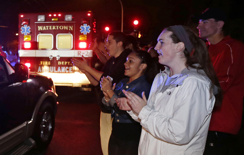 A gathering of people applaud as first responders leave the scene after the arrest of a suspect of the Boston Marathon bombings in Watertown, Mass., Friday, April 19, 2013. Two suspects in the Boston Marathon bombing killed an MIT police officer, injured a transit officer in a firefight and threw explosive devices at police during their getaway attempt. (AP Photo/Charles Krupa)