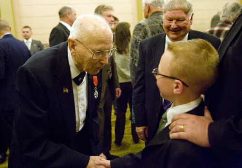 Kim Raff  |  The Salt Lake Tribune (left) Mike Kladis, 91, shakes hands with (right) Ryan Sanders after be awarded the Legion of Honour, for his service in the Army liberating France during World War II, by the Honorary Consul of France at the Masonic Lodge in Salt Lake City on April 20, 2013.  This award is France's highest honor.