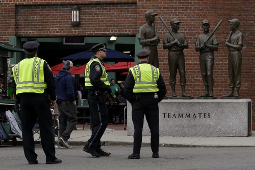 Police officers stand near statues of former Boston Red Sox greats, from left, Ted Williams, Bobby Doerr, Johnny Pesky and Dom DiMaggio during a baseball game between the Kansas City Royals and the Boston Red Sox, the first game held in the city following the Boston Marathon explosions, Saturday, April 20, 2013, in Boston.  Police captured Dzhokhar Tsarnaev, 19, the surviving Boston Marathon bombing suspect, late Friday, after a wild car chase and gun battle earlier in the day left his older brother dead. (AP Photo/Julio Cortez)