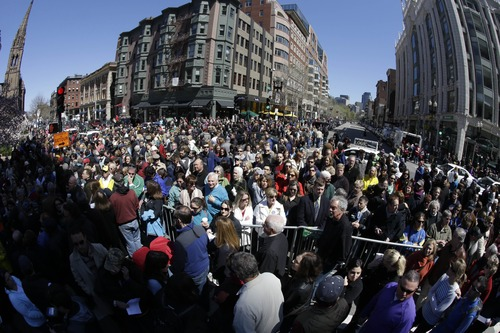 In this photograph made with a fisheye lens, people attend an interfaith service held near a makeshift memorial on Boylston Street, near the finish line of the Boston Marathon, Sunday, April 21, 2013, in Boston. The city is coping in the aftermath of the marathon bombing. (AP Photo/Julio Cortez)