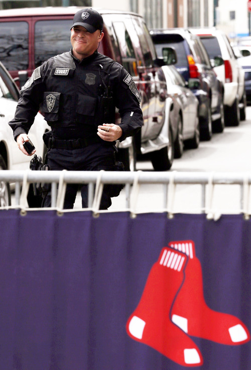 An official wearing SWAT gear walks behind a fenced off area outside of Fenway Park during a baseball game between the Kansas City Royals and the Boston Red Sox, the first game held in the city following the Boston Marathon explosions, Saturday, April 20, 2013, in Boston. Police captured Dzhokhar Tsarnaev, 19, the surviving Boston Marathon bombing suspect, late Friday, after a wild car chase and gun battle earlier in the day left his older brother dead.  (AP Photo/Julio Cortez)