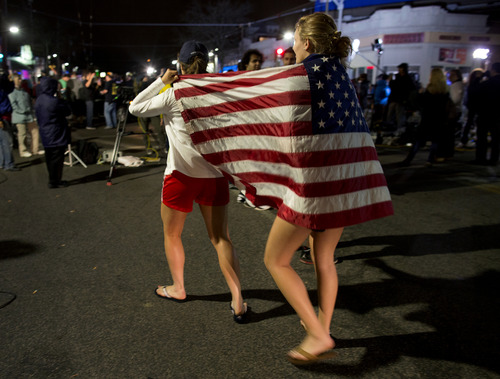 Taylor Richard, center, of Belmont, Mass., and Alyssa Kohler, 17, of Cambridge, Mass., wrap themselves in the American Flag in Watertown, Mass., Friday, April 19, 2013.  A 19-year-old Massachusetts college student wanted in the Boston Marathon bombing was captured hiding out in a boat parked in a backyard Friday and his older brother lay dead in a furious 24-hour drama that transfixed the nation and paralyzed the Boston area with fear. (AP Photo/Craig Ruttle)