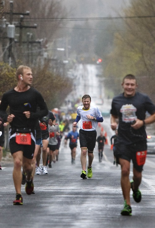 Leah Hogsten  |  The Salt Lake Tribune Graeme Tindall (center) runs with his fellow marathoners along 2300 east in Holladay. Soggy conditions hardly dampened the festive mood the 7,000 runners participating in the Salt Lake City Marathon, which started Saturday morning, April 20, 2013, following a moment of silence in honor of those harmed five days earlier at the Boston Marathon bombing