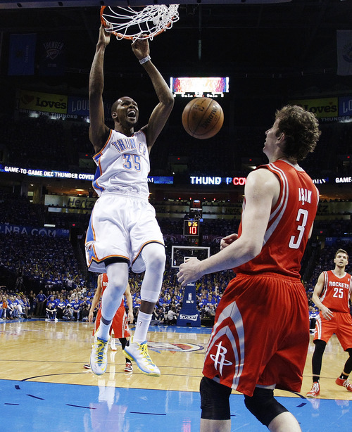 Oklahoma City Thunder forward Kevin Durant (35) dunks in front of Houston Rockets center Omer Asik in the first quarter of Game 1 of their first-round NBA basketball playoff series in Oklahoma City, Sunday, April 21, 2013. (AP Photo/Sue Ogrocki)