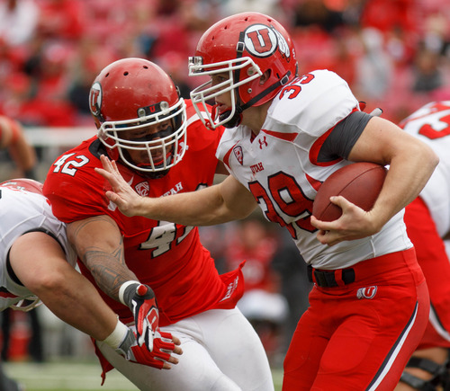 Trent Nelson  |  The Salt Lake Tribune Andrew Fletcher runs the ball, as LT Filiaga closes in during the University of Utah's Red-White Spring football game, Saturday April 20, 2013 in Salt Lake City.