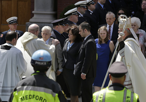 Elise Amendola  |  The Associated Press A priest comforts family members of Boston Marathon bomb victim Krystle Campbell after her funeral at St. Joseph's Church in Medford, Mass. Monday, April 22, 2013. At center is her mother, Patty Campbell, and her brother, Billy. At far right is Boston Cardinal Sean O'Malley.
