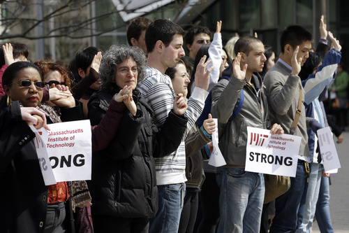 People raise their arms while observing a moment of silence for those killed in the Boston Marathon bombings and form a human chain from a makeshift memorial for fallen MIT police officer Sean Collier to a campus police station, at MIT, in Cambridge, Mass., Monday, April 22, 2013. Collier was fatally shot on the MIT campus Thursday, April 18, 2013. Authorities allege that Boston Marathon bombing suspects Tamerlan and Dzhokhar Tsarnaev were responsible. (AP Photo/Steven Senne)