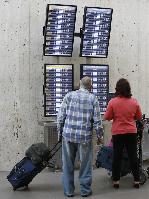 Traveler Jay Mortimer, left,  checks his flight status at LAX International airport in Los Angeles Monday, April 22, 2013.  The FAA said late Sunday night that staffing cuts were causing delays averaging more than three hours for flights arriving at Los Angeles International Airport.   (AP Photo/Damian Dovarganes)